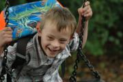 Junge mit Down-Syndrom mit Schulranzen auf der Schaukel